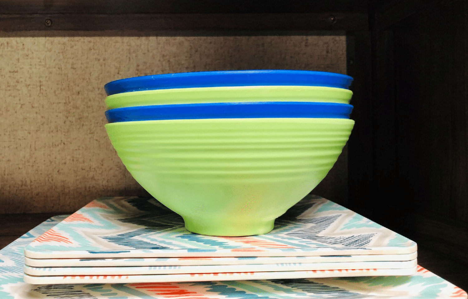 Green and blue stacked bowls atop square dishes with a Navajo pattern.