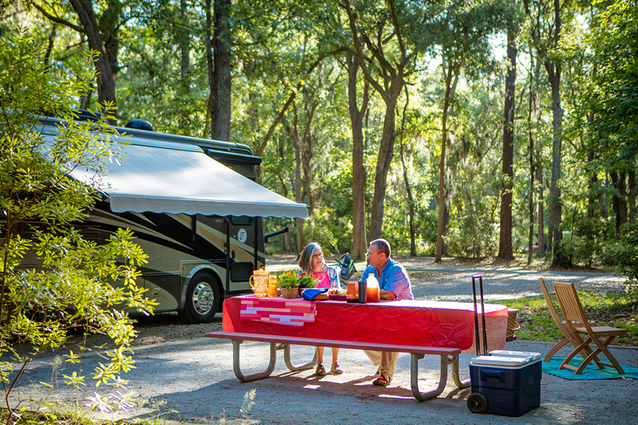 A couple sit at a campsite picnic table with motorhome in background.