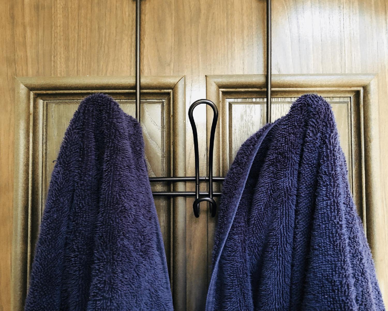 Purple towels hanging from an over-the-door hanger.