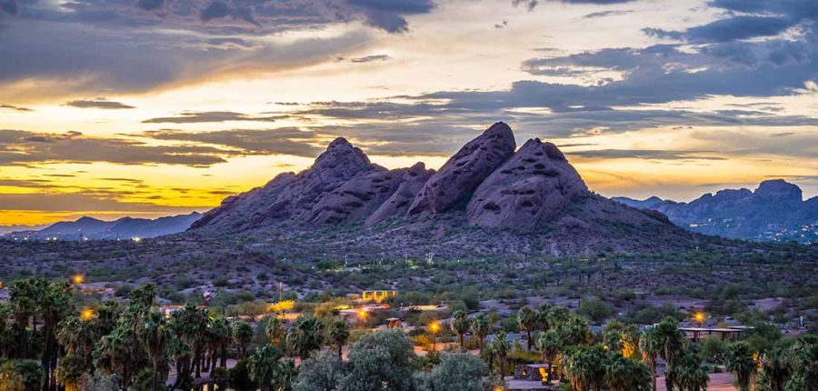 A rock outcropping looms over a desert community as dusk light glimmers on the horizon.