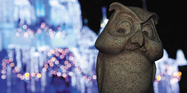 Owl from Winnie the Pooh looks down at the crowd with lights in the background.
