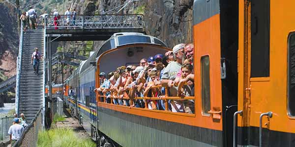 Visitors in an orange open car aboard the Royal Gorge Route Railroad