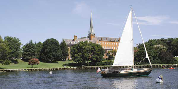 A single-masted sailboat glides past a church with New England-style spire.