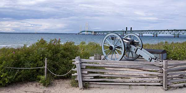 A cannon points out to a great lake with a bridge in background.