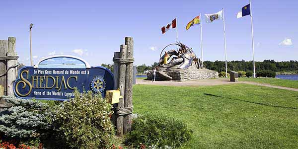 "A sign proclaims, ""Shediac"" as flags wave in the background behind a majestic lobster statue."
