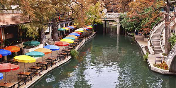 A river winds through a town with colorful umbrellas on one bank.