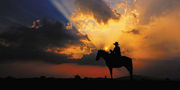 A cowboy on horseback stand on a ridge with sun setting in the background.