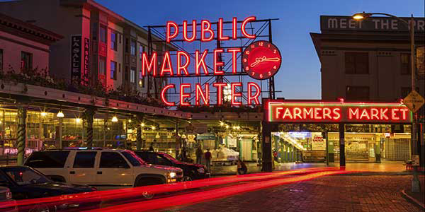 Red neon light illuminates a Farmers Market during evening.
