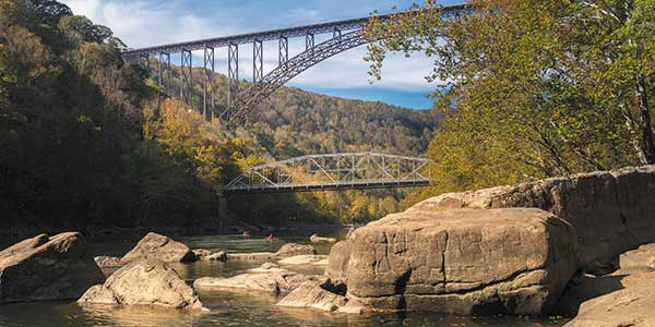 Large iron bridge with arch support spans wide river valley.