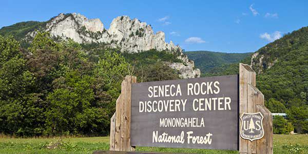Sign indicating Seneca Rocks with craggy stone in background.