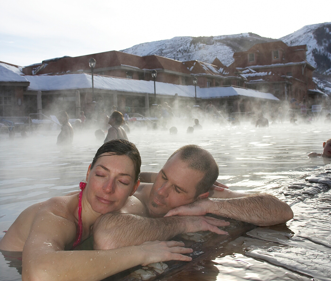 A man and woman relax in a natural hot springs.