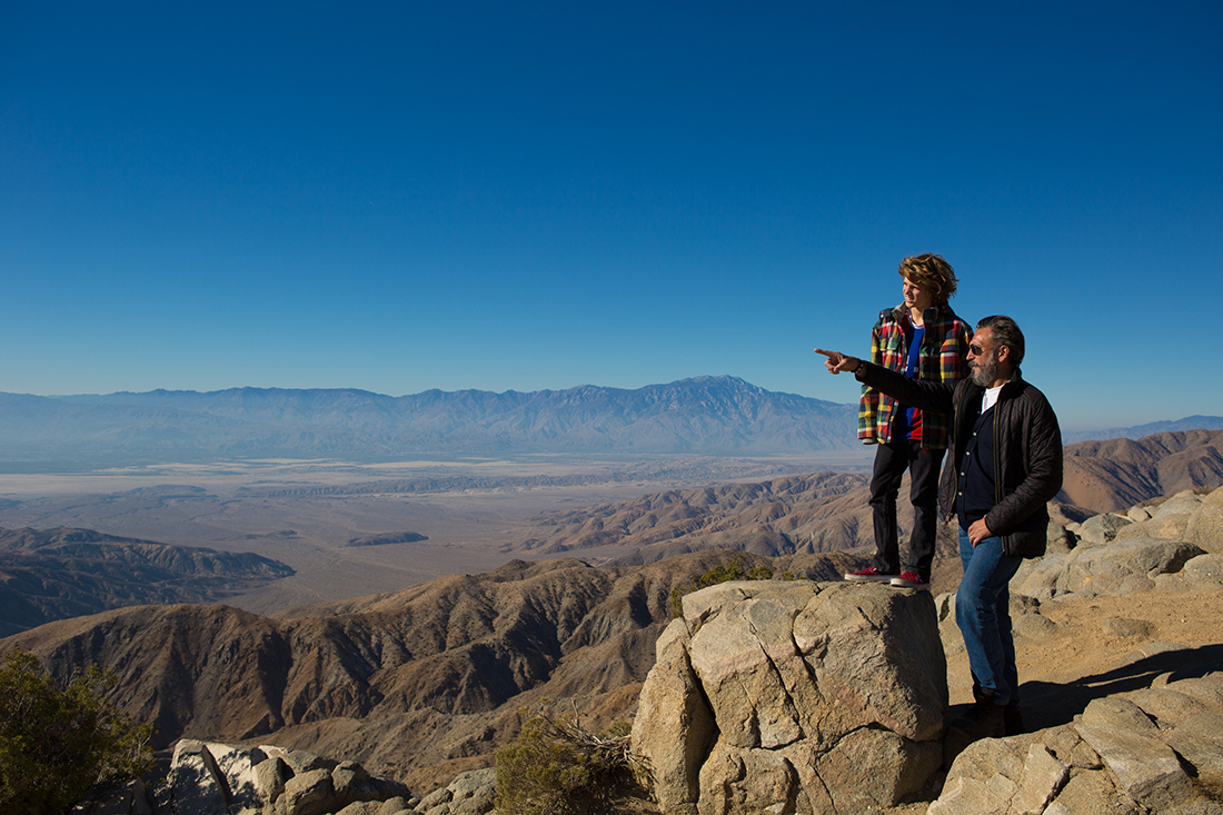A middle-aged man shows a child a stunning view over Joshua Tree.