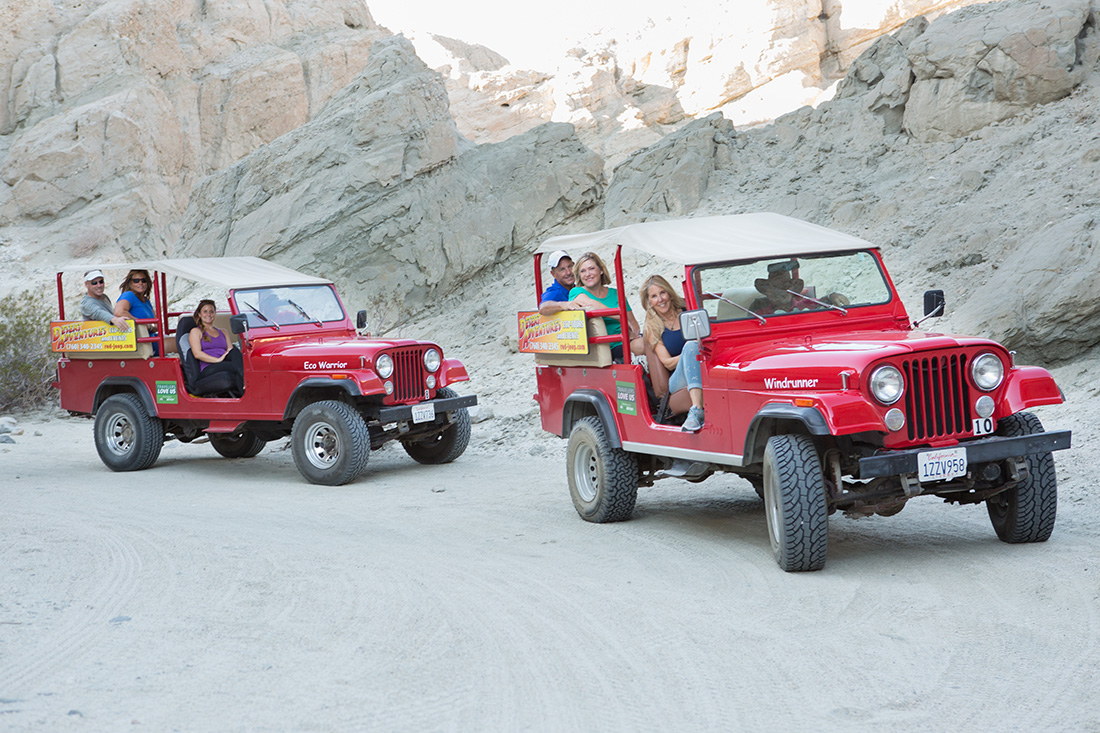 A pair of red jeeps transport passengers through a desert ravine.