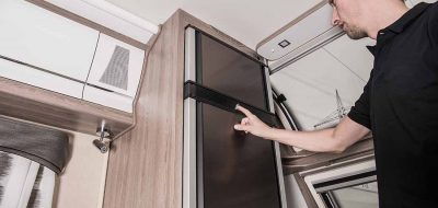 replacing RV refrigerator — man checks tall, thing fridge in motorhome.