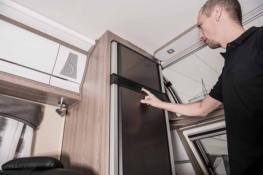 replacing RV refrigerator —man checks tall, thing fridge in motorhome.