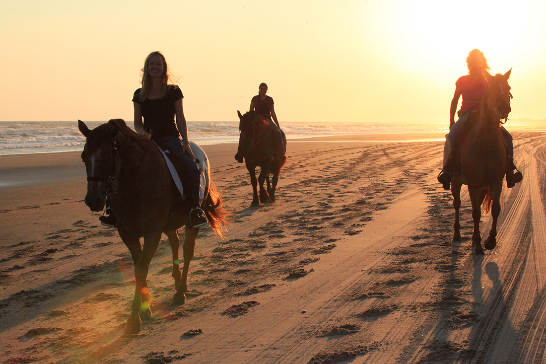 Three women ride horses at sunset.