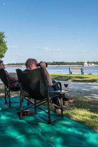 Tom Sawyer's RV park A couple gaze out at a wide river with binoculars.