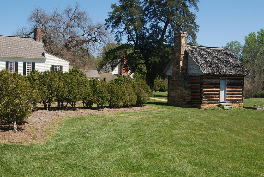 Colonial era structures stand on the edge of a lawn.