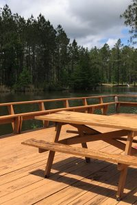 Sunroamers RV Resort is now rated — A picnic table on a patio overlooking a lake.