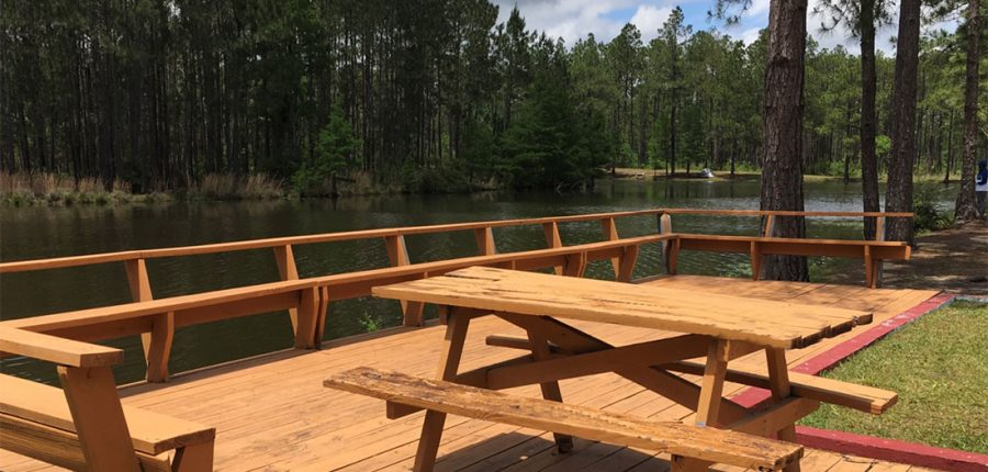 Sunroamers RV Resort is now rated —A picnic table on a patio overlooking a lake.