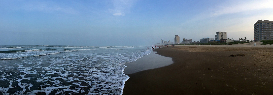 A beach with a broad shoreline overlooked by high-rise hotels.