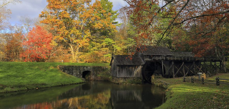 A mill on a grassy bank overlooking a stream amid fall foliage.