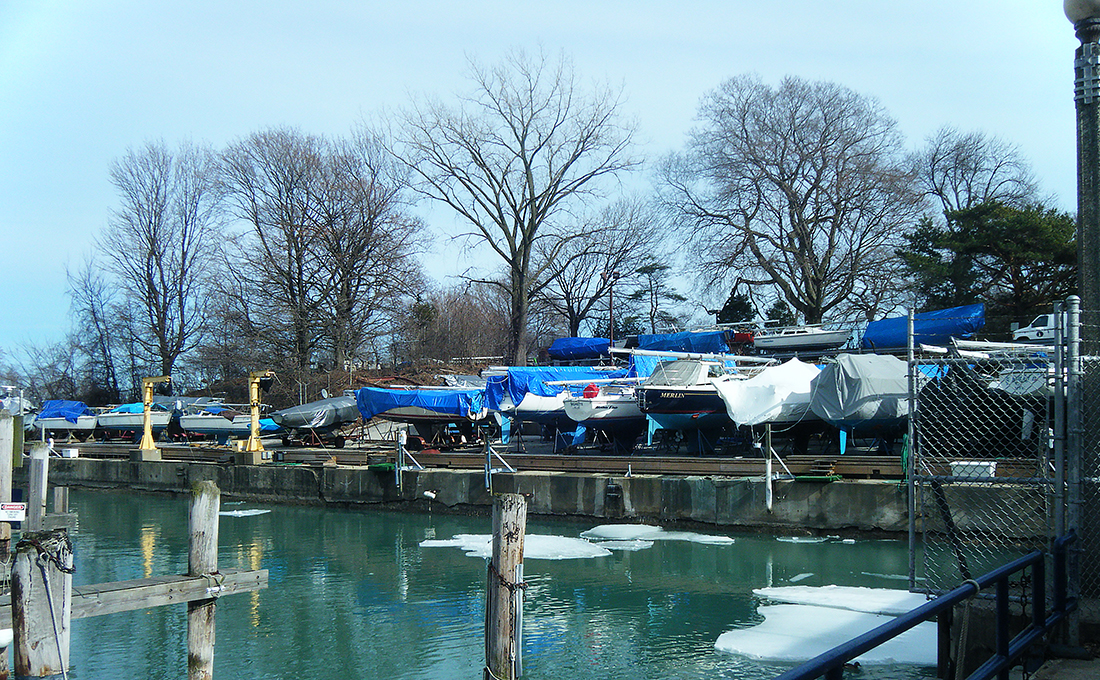 Boats parked in winter storage on the banks of a channel.