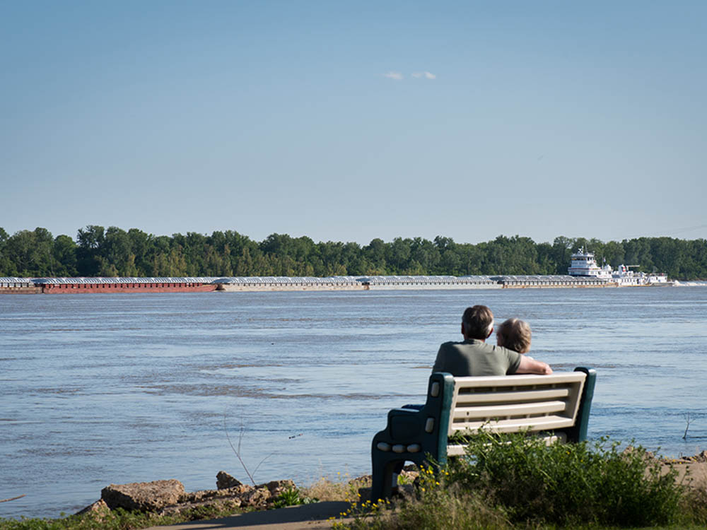 A couple on a bench watch a barge churn past.