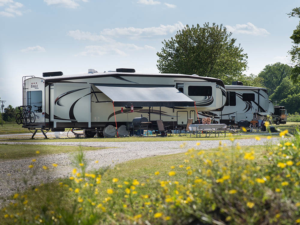 A fifth-wheel trailer parked in an ample site.