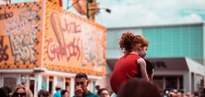 Young daughter with red hair on Dad's shoulders at OKC Fair, walking in crowd