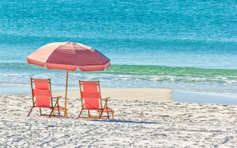 A pair of chairs on the beach.