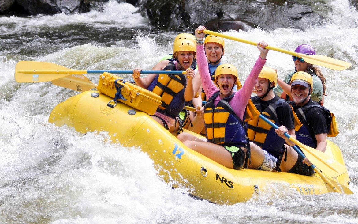 Group of six people on yellow raft smiling and posing going down Pigeon River