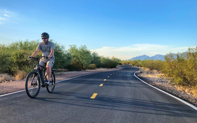A man rides a bike along a desert highway.