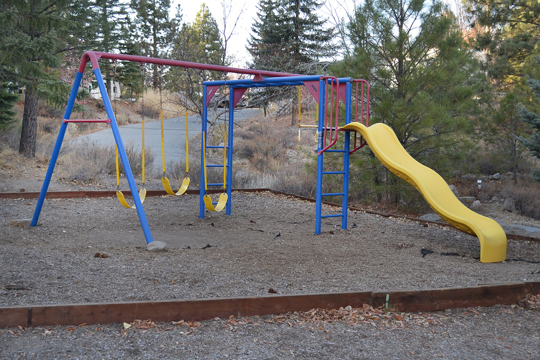 Campground playground surrounded by forest.
