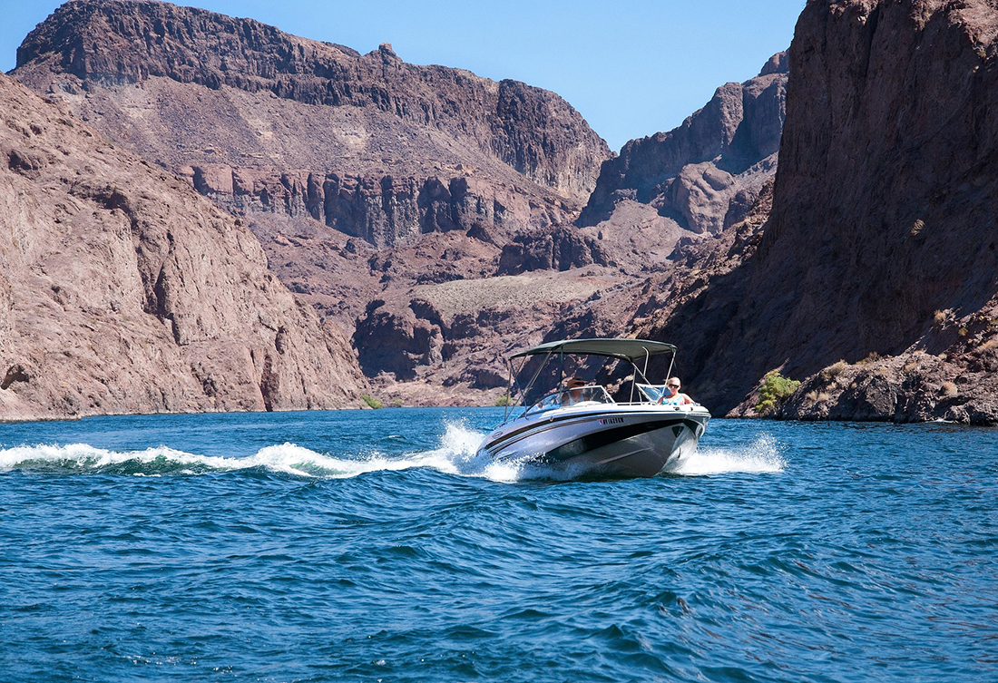 A boat skimming on a lake under towering cliffs.