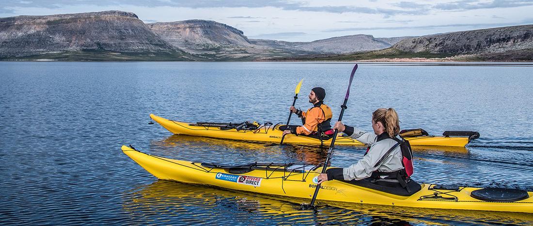 A couple paddles kayaks across a vast lake.
