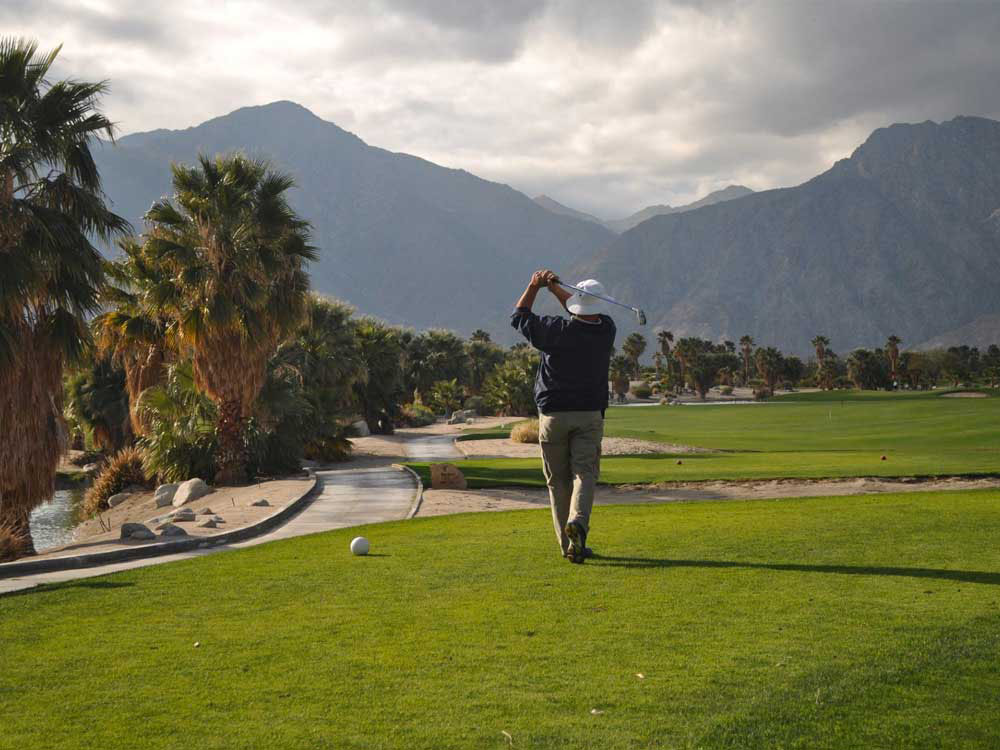 Golfer drives from the tee with mountains in background.