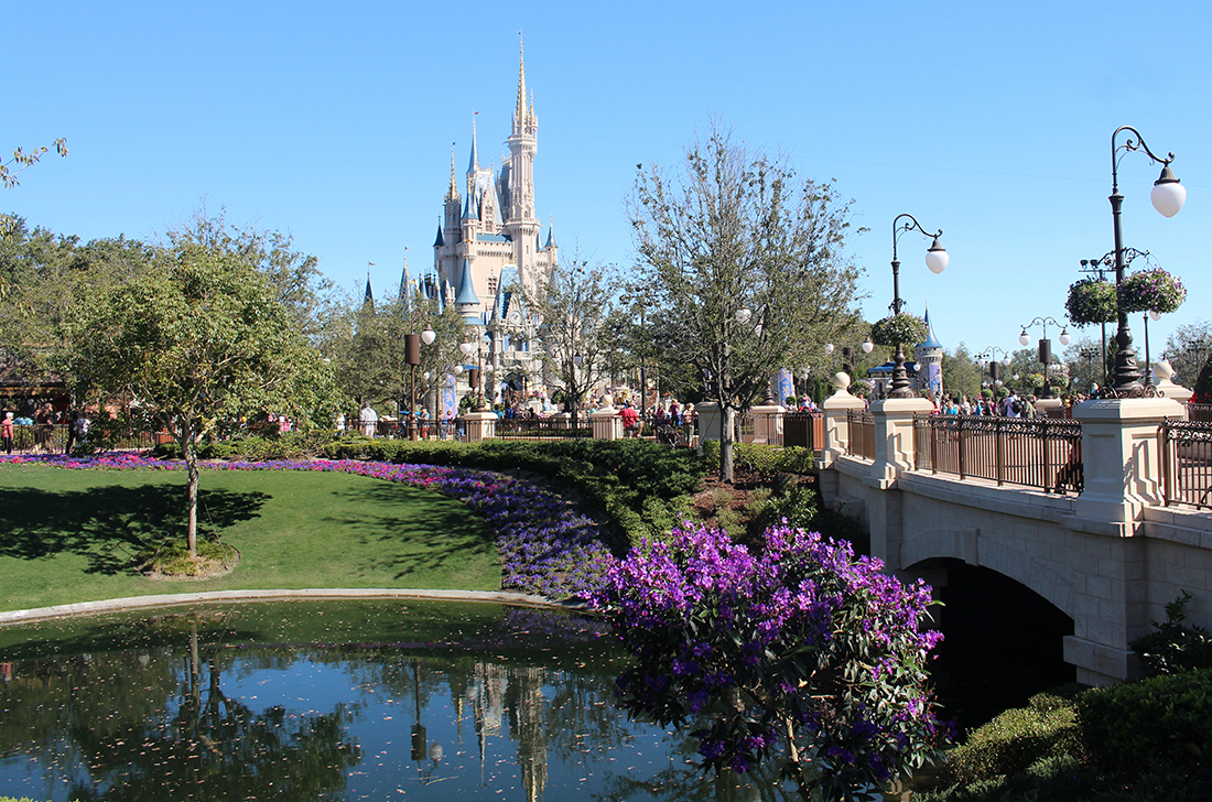 Cinderella's castle rises majestically in the background as bridge crosses river.