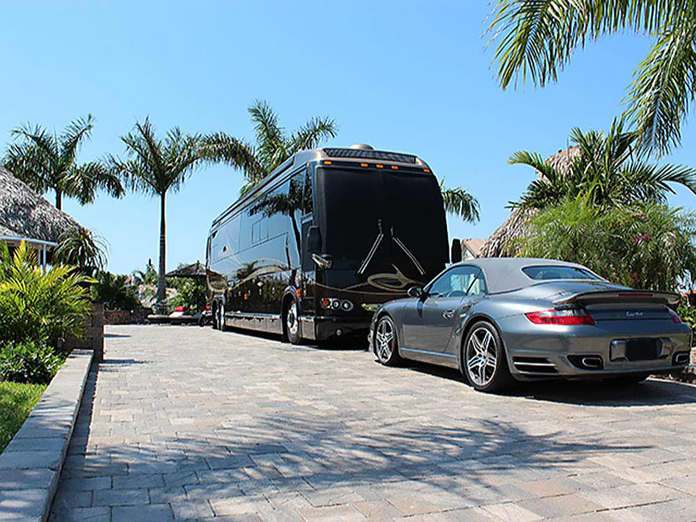 A Porsche parked next to a luxury motorhome.