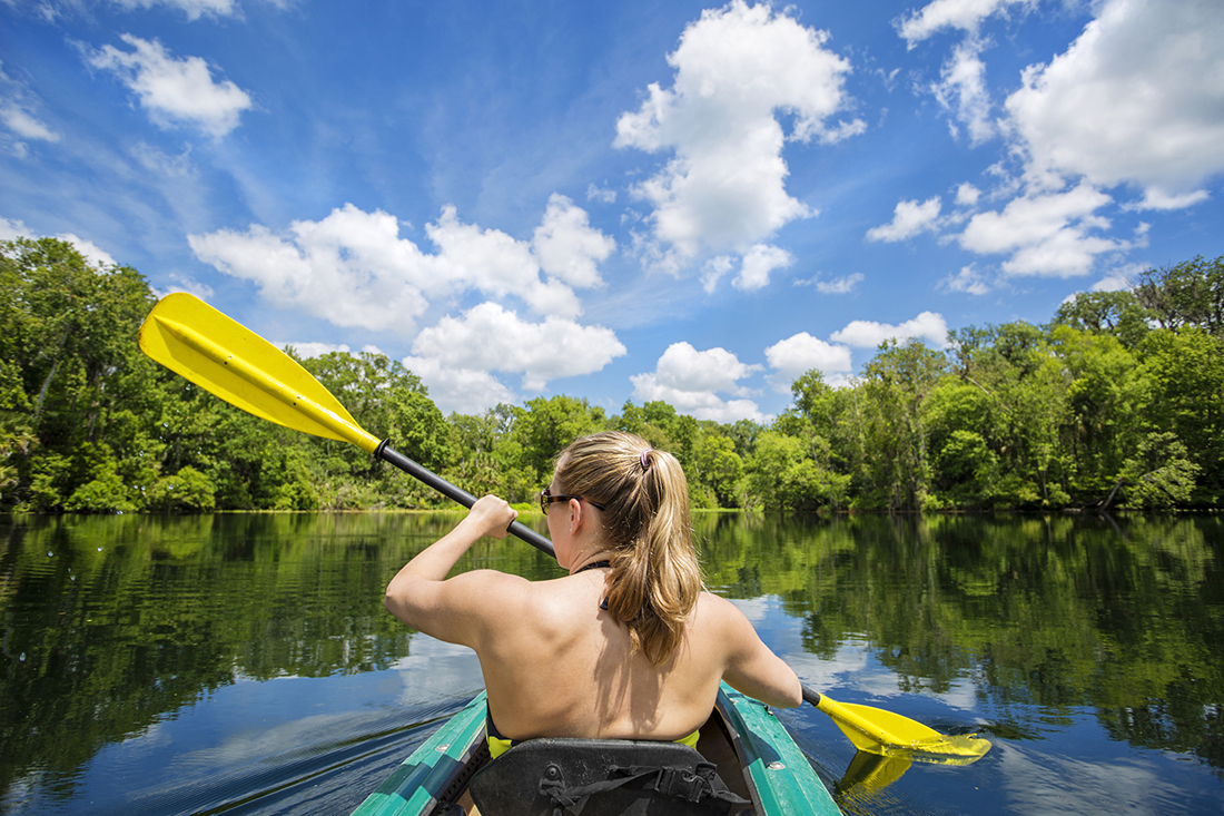 Woman kayaking along a beautiful tropical jungle river.