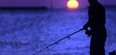 An angler stands at water's edge at sunset.