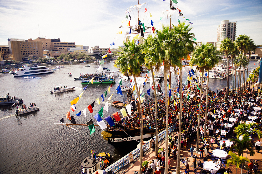 Pirate ships flock in a harbor for a Pirate festival.