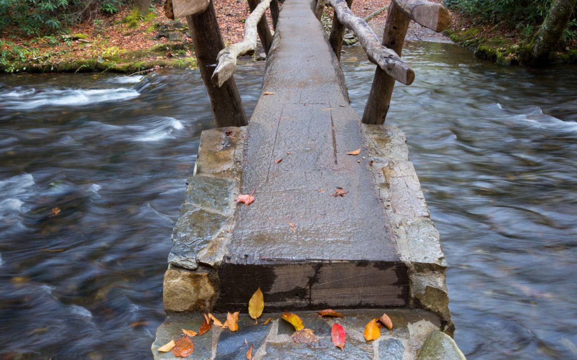 Narrow foot bridge over a stream with Fall colors