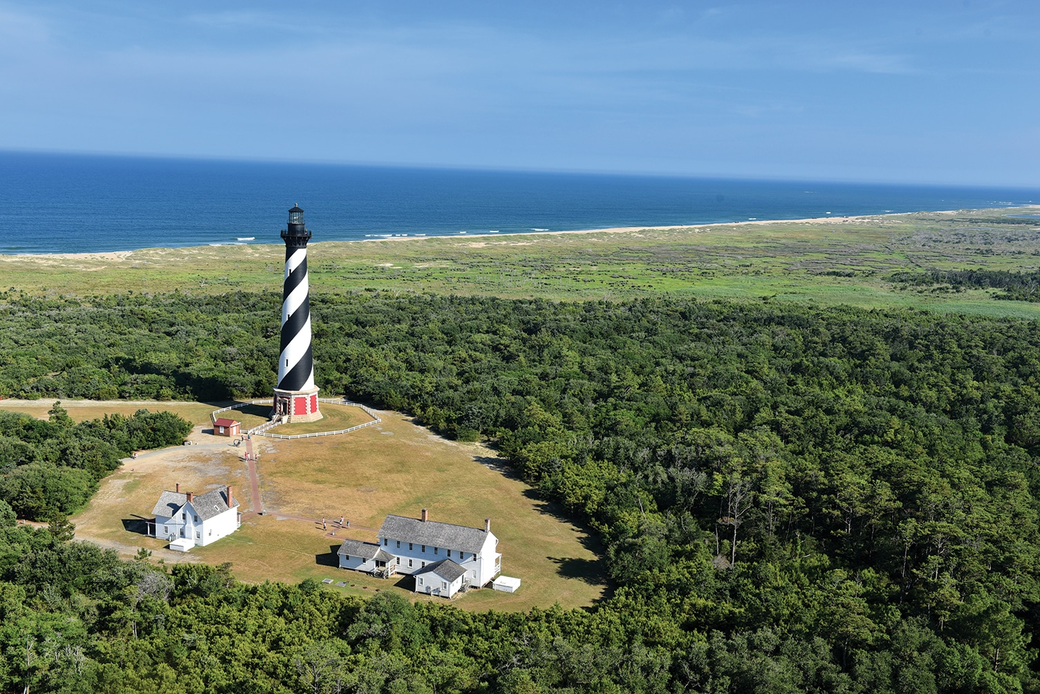 Aerial view of black and white swirl designed brick lighthouse in North Carolina