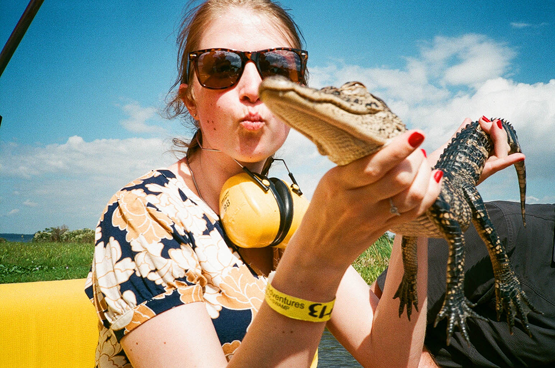 An airboat passenger holds a little gator during an airboat tour.