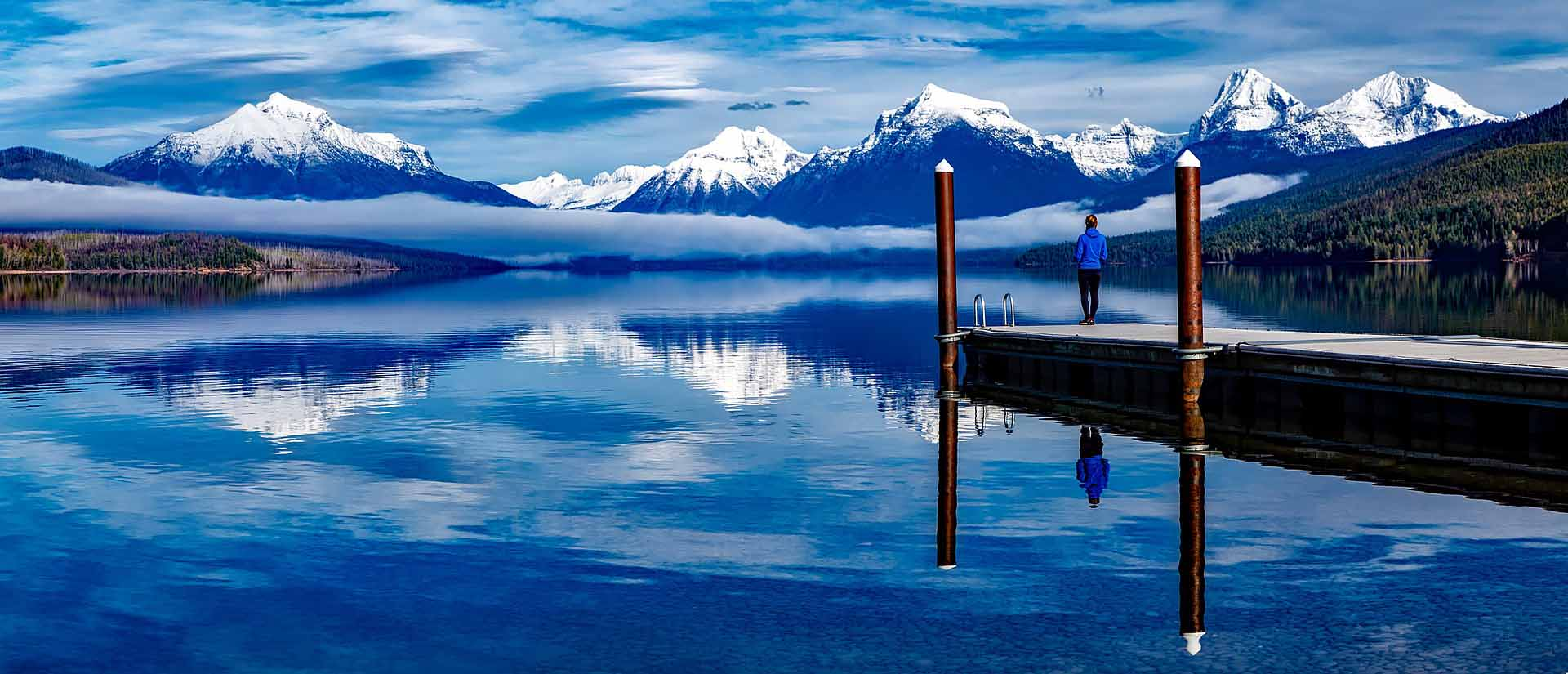 A woman gazes out on a lake that reflects snow-peaked mountains on the horizon.
