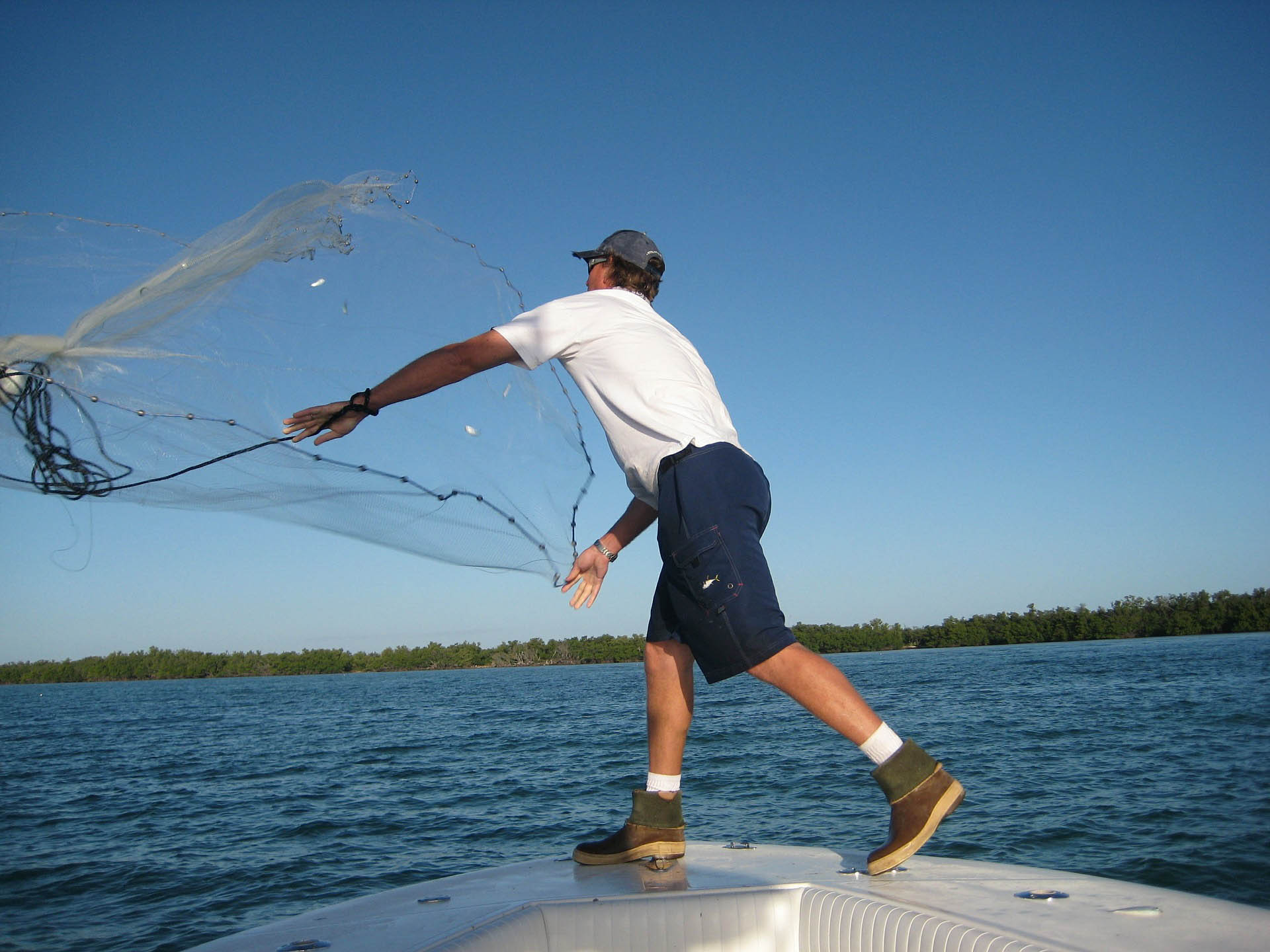A fisherman casts a net over the side of a boat.