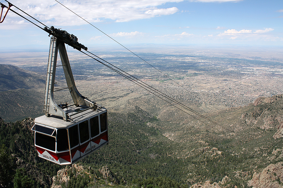 A white and red tram rides a cable over a mountainous terrain.