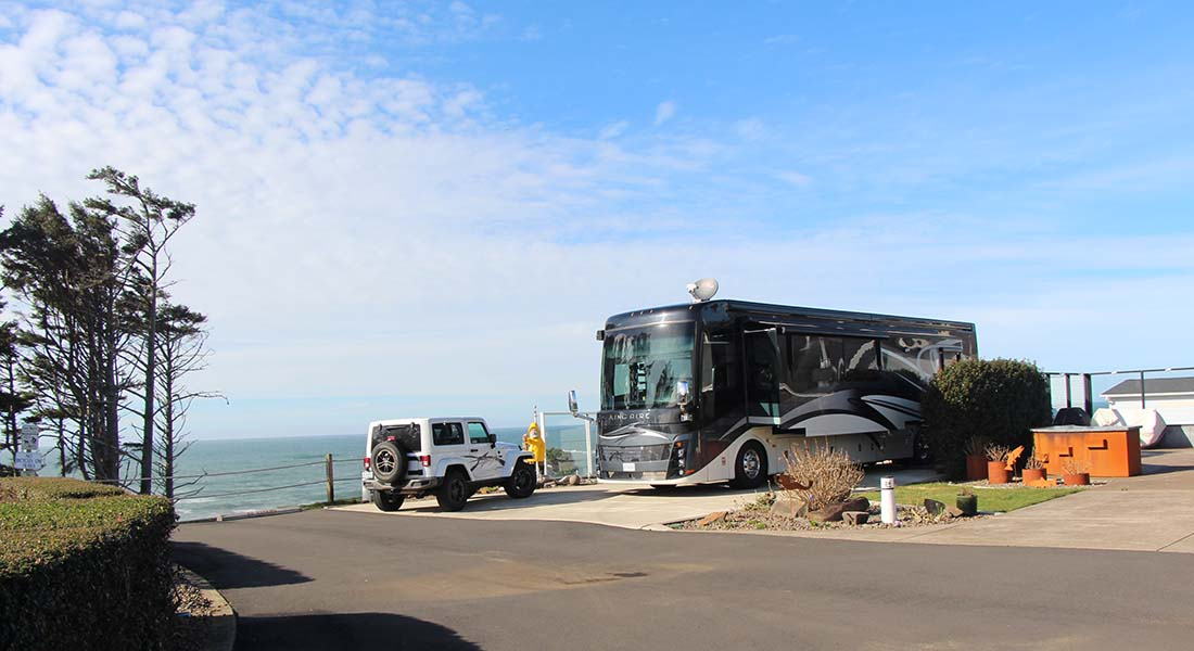 An RV and white jeep parked on a bluff overlooking the ocean.