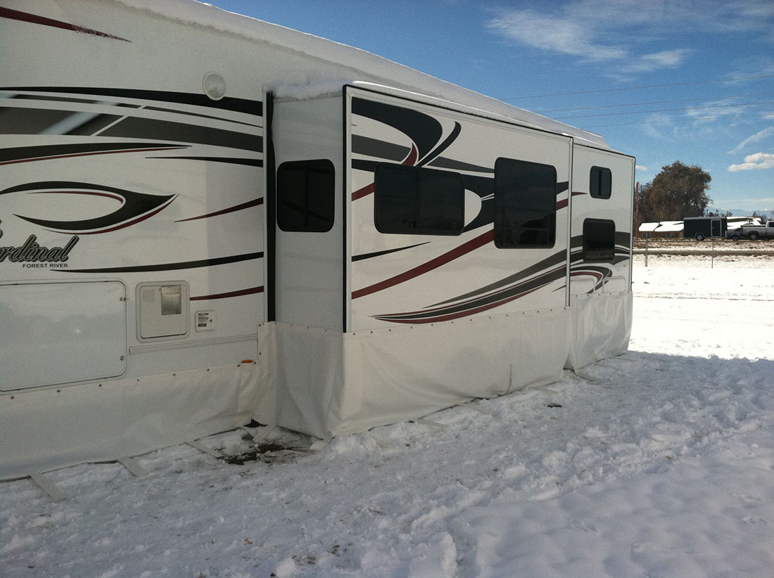 An RV with a skirt attached in a snowy landscape.